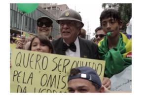 Jovens marcham ao lado de militar da ditadura.